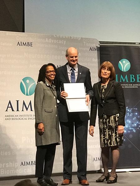 Dr. Grist receiving AIMBE fellowship certificate
